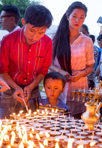 祈りの燈明を灯す若い夫婦